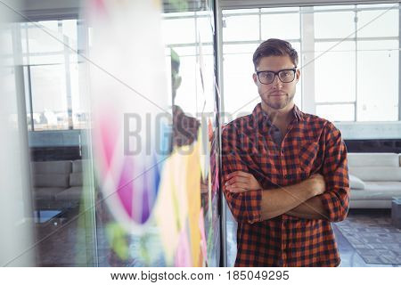 Portrait of serious businessman standing by adhesive notes in creative office