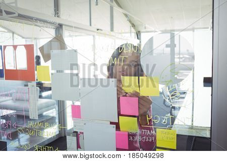 Young businesswoman seen through adhesive notes on glass in creative office