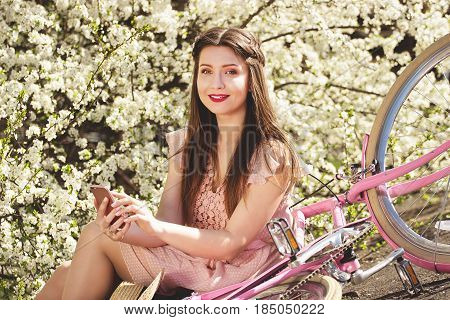 Smart Gadget. Portrait Of Young And Beautiful Long-haired Girl In Pink Dress Sitting With Retro Bike