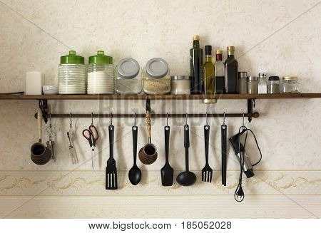 glass bottles of oils jars of condiments salt spices on the shelf spatulas spoons ladle dipper for coffee scissors kitchen utensils hanging along the wall on hooks jars with flour sugar rice cereals corkscrew blender