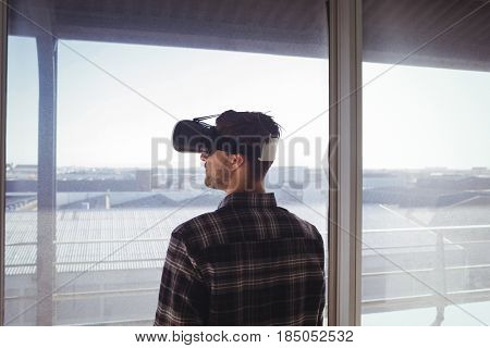 Rear view of businessman wearing virtual reality headset in office