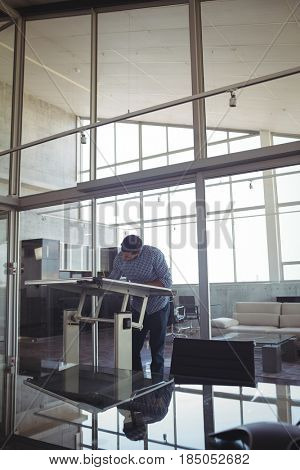 Male interior designer drawing on workbench in office seen through glass
