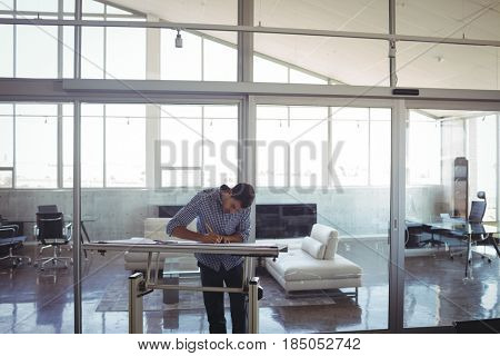 Focused male interior designer drawing on workbench in office
