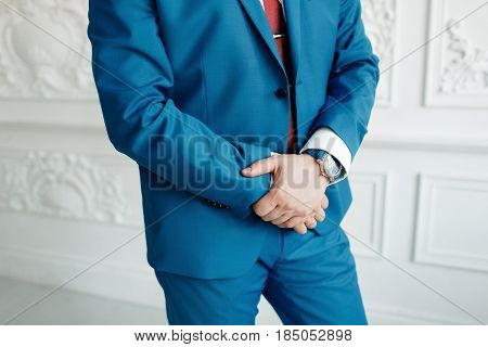 Crossed man's hands in a blue jacket. Cuff and hand watch mechanical.