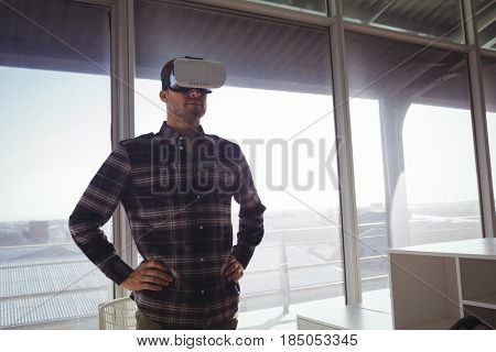 Confident businessman wearing virtual reality headset in office
