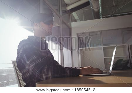 Low angle view of businessman wearing virtual reality headset while using laptop in office