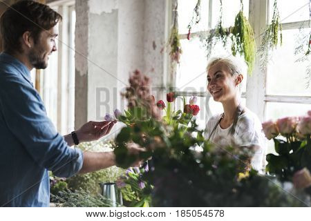 Flower shop owner talking with customer