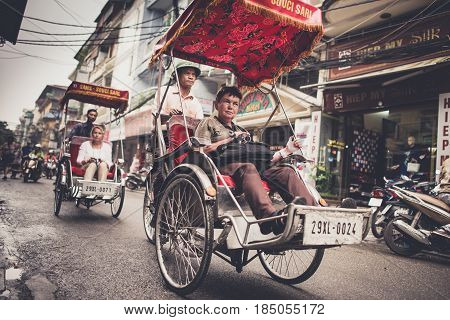 HANOI, VIETNAM - DECEMBER 01: An unidentified tourist sits in traditional cycle vehicle in the busy Hanoi traffic on December 01, 2012 in Hanoi, Vietnam