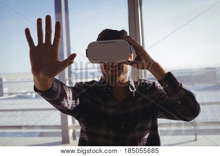 Young businessman experiencing virtual reality in creative office