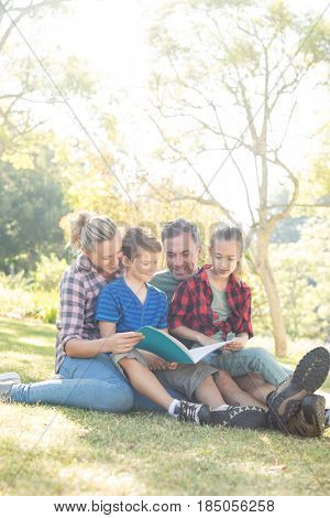 Family reading a book in the park on a sunny day