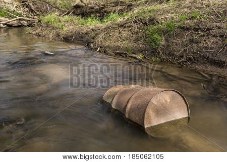 A rusty metal barrel in a creek.