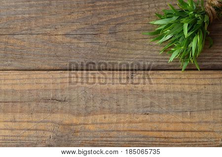 Bunch of fresh tarragon on a wooden background with a space for note