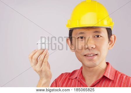 Engineer Wear Red Shirt And Yellow Engineer Hat Holding House