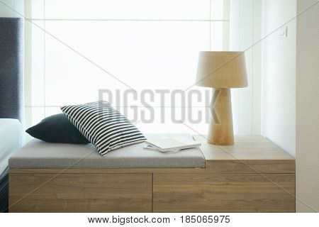Pillows And Reading Lamp On Cozy Seat By The Window Next To Bed