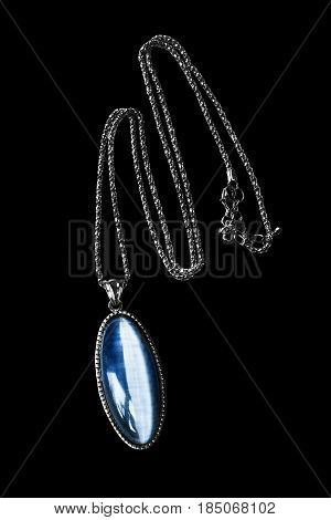 Vintage sapphire medallion on silver chain isolated over black