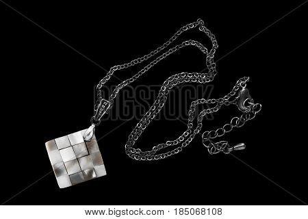 Elegant nacre pendant on silver chain on black background