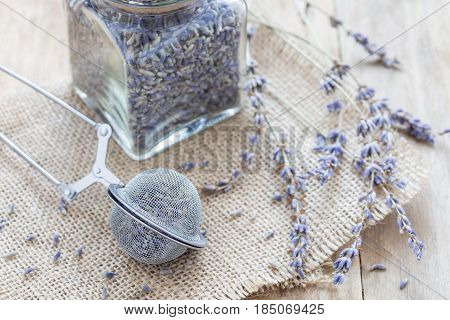 Dry lavender tea in tea infuser spoon and glass jag on wooden background horizontal