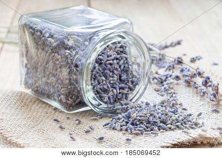Dry lavender tea in glass jag and on wooden background horizontal