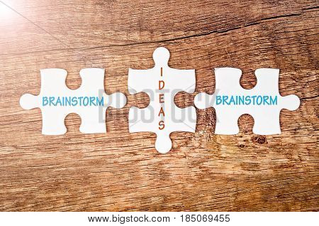 Brainstorm and ideas words on jigsaw puzzle on wooden background Business concept