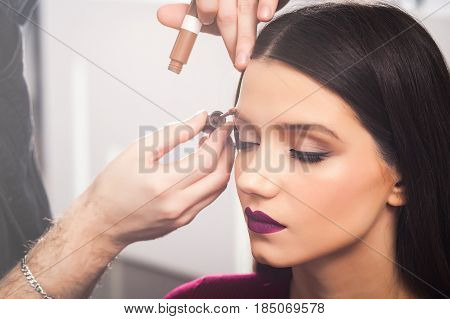 cool male make-up artist Colors eyebrows to brunette girl in a dress in beauty salon, close up