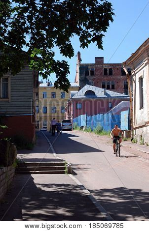 VYBORG RUSSIA - JULY 10 2016: Street scene at noon with natives in one of the old fashioned Vyborg neighbourhoods
