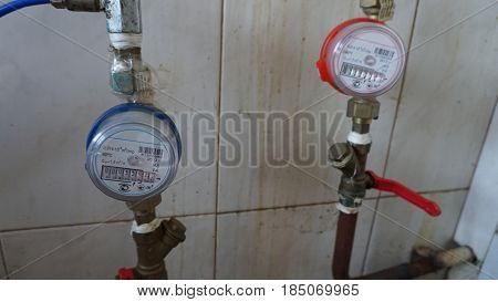 Gas meters for cold and hot water against dirty tiles.