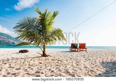 Empty wooden beach chairs on the beach with coconut tree in Phuket Thailand
