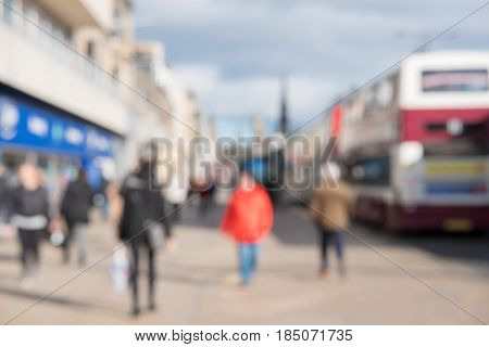 Blurred Image Of People Walking On The Street, With Car, Building In Background. On Princes Street,
