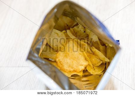 Potato crisps in package on wooden table