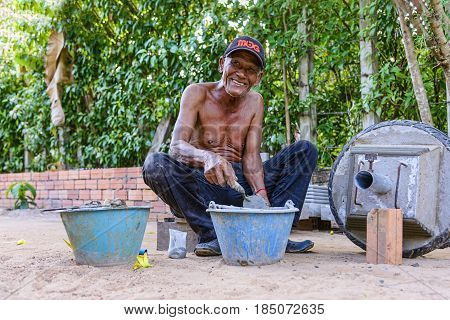 Siem Reap, Cambodia - January 5, 2017: Portrait of an unidentified elder Khmer man working with cement