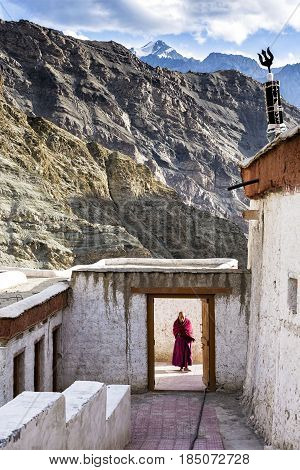 Rizong, India - August 17, 2015: A Buddisth monk wait for visitors at the entrance of Rizong Monastery. It is situated at the top of a rocky side valley on the north side of the Indus river