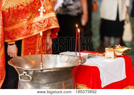The font with candles for the christening of children in the Orthodox Church.