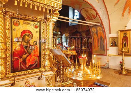 Interior of Orthodox church. Symbolic Orthodox gold cross with the crucifixion of Jesus golden candleholders and other details.