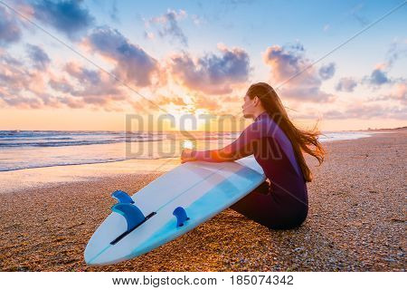 Beautiful surfer girl with surfboard on the beach at sunset