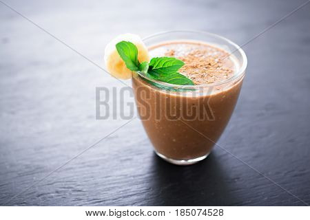 Chocolate banana smoothie on dark background. Fresh milkshake and mint