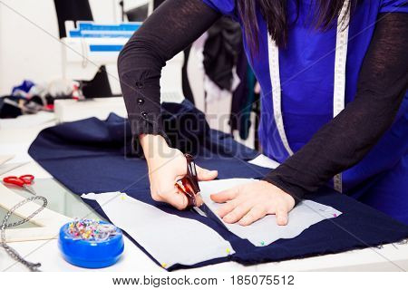 a female fashion designer is working on a new piece of clothing in her somewhat chaotic studio. in this shot, she is cutting out pieces of cloth using some sewing patterns.