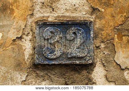 Old retro weathered cast iron plate with number 32 closeup
