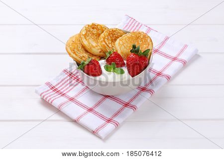 bowl of american pancakes with white yogurt and fresh strawberries on checkered dishtowel
