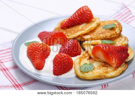 plate of american pancakes with white yogurt and fresh strawberries on checkered dishtowel - close up