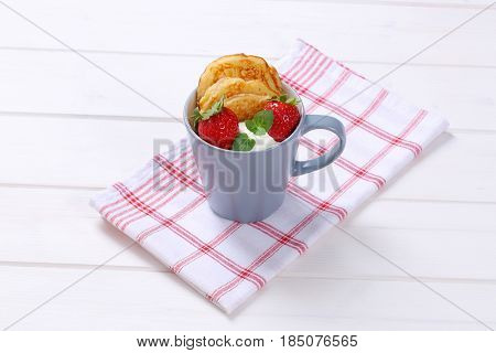 cup of american pancakes with white yogurt and fresh strawberries on checkered dishtowel