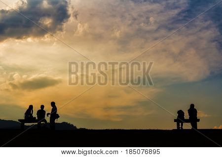 Silhouette of people sitting on bench in evening