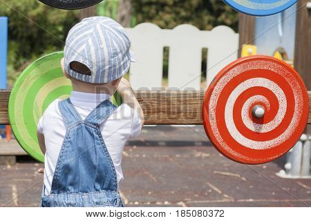 2 year-old boy playing with wooden colored disc with spiral draw in motion. Playground toy