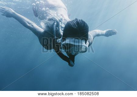 Female free diver swimming underwater with mask and snorkel.