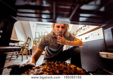 Young man taking burnt pizza from stove