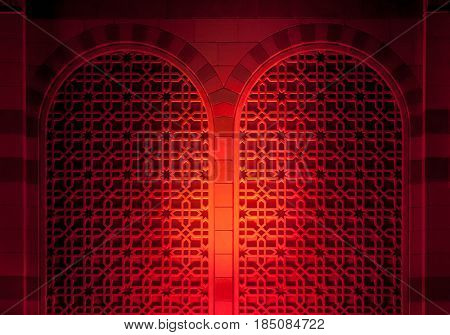 An intricate relied work, an islamic pattern done on a facade of a building. Bright red spot light thrown a decorative mosque wall.