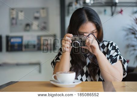 woman using film camera retro hipster style in coffee shop with hot coffee / woman and camera