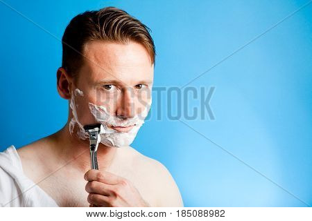 a man is shaving in front of a blue background