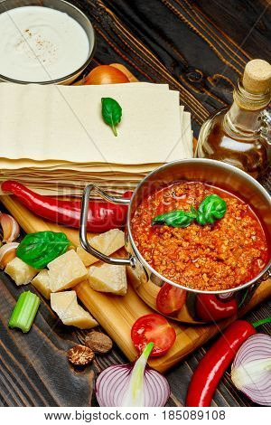 lRecipe of lasagna - pasta sheets, bolognese and bechamel sauce on wooden table