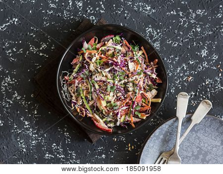 Red cabbage coleslaw with poached chicken. Healthy food concept. Salad with red cabbage carrot pepper radish and boiled chicken on a dark background top view