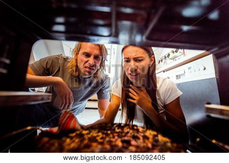 Young woman taking burnt pizza from stove